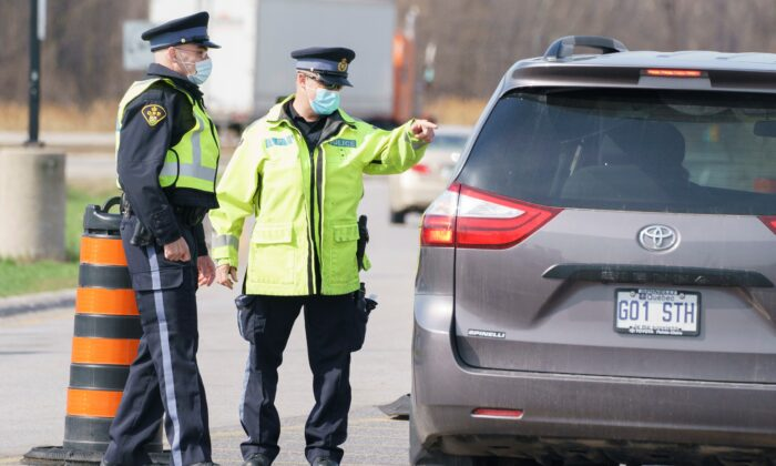 Motorists are screened at a police checkpoint to limit non-essential travel from