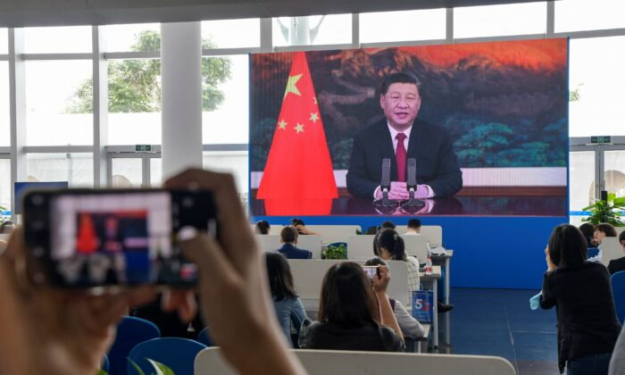 Journalists watch a screen showing China's Leader Xi Jinping delivering a speech during the opening of the Boao Forum for Asia (BFA) Annual Conference 2021 in Boao, Hainan province, China, on April 20, 2021. (STR/AFP via Getty Images)