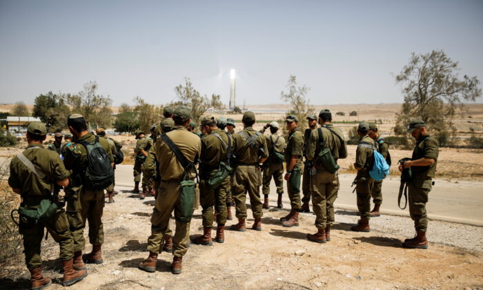Israeli soldiers gather as they survey the area after a Syrian missile exploded in southern Israel, the Israeli military said, in Ashalim, southern Israel, on April 22, 2021. (Amir Cohen/Reuters)