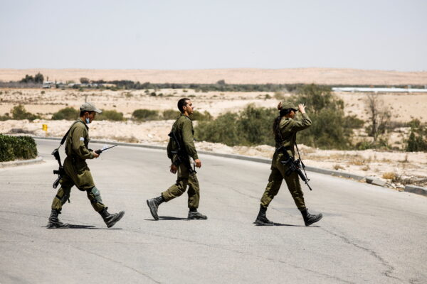 Israeli soldiers survey the area after a Syrian missile exploded in southern Israel, the Israeli military said, in Ashalim