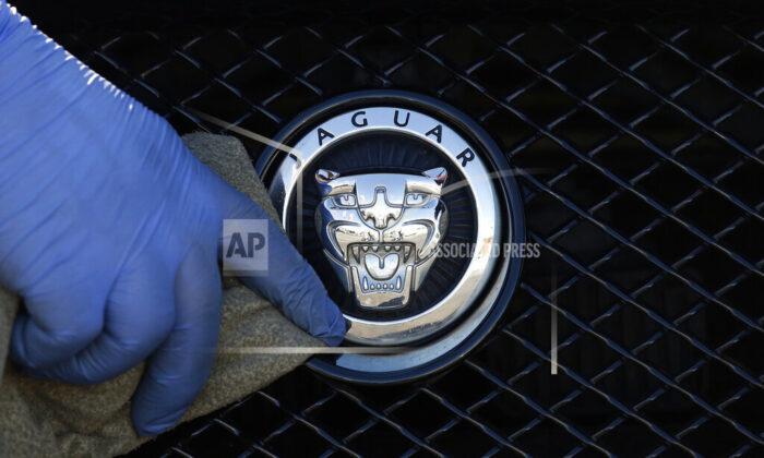 A worker polishes a Jaguar logo on a car at a Jaguar dealer in London, UK, on Wednesday Sept. 28, 2016. (Frank Austin/AP Photo file)