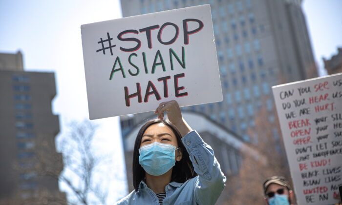A woman holds a placard as she participates in a Stop Asian Hate rally at Columbus Park in New York City, N.Y., on April 3, 2021. (Reuters/Jeenah Moon)