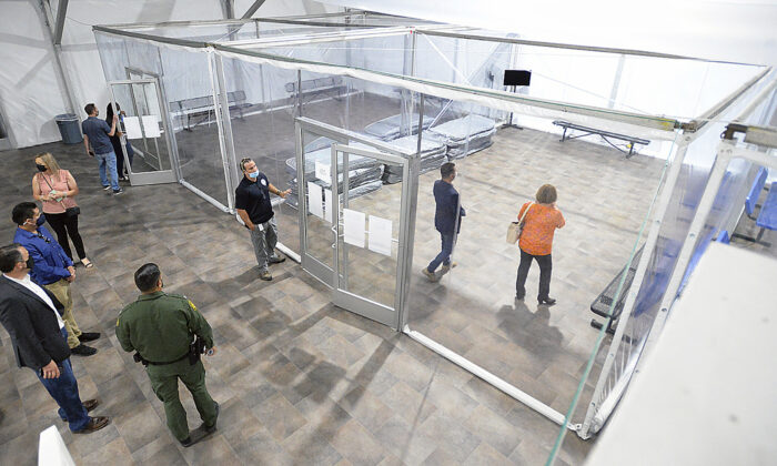 People touring the U.S. Border Patrol Yuma Sector, soft-sided processing facility, look at the pods inside one of four living areas at the facility, in Yuma, Ariz., on April 20, 2021. (Randy Hoeft/The Yuma Sun via AP)