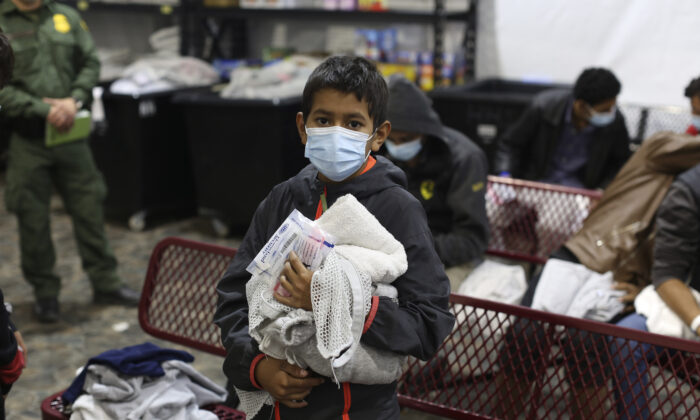 A young migrant waits for his turn to take a shower at the Department of Homeland Security holding facility in Donna, Texas, on March 30, 2021. (Dario Lopez-Mills/Pool/Getty Images)