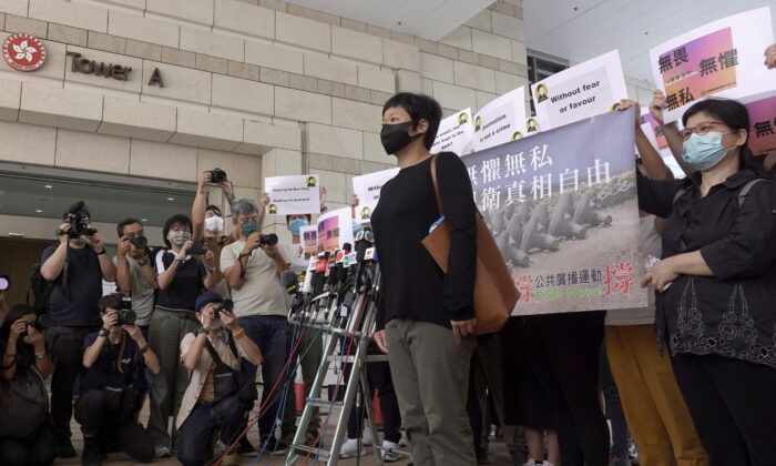Bao Choy Yuk-Ling, a freelance journalist with RTHK, poses for pictures outside West Kowloon Magistrates' Courts as she arrives for charges of making a false statement to obtain data for a documentary on the police's handling of a mob attack, in Hong Kong, China, on April 22, 2021. (Pak Yiu/Reuters)