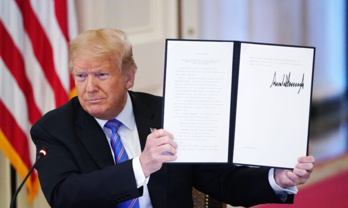 "President Donald Trump holds an executive order he signed at the White House in Washington on June 26, 2020 to establish a 20-person Advisory 1776 Commission under the Department of Education to promote ""patriotic education."" The commission was terminated by President Joe Biden on Jan. 20, 2021. (Mandel Ngan/AFP via Getty Images)"