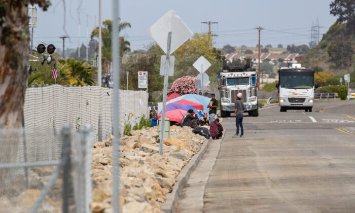 Homeless people gather near a tent, at the end of a strip formerly used for camping but now covered with rocks, in Oceanside, Calif., on April 14, 2021. (John Fredricks/The Epoch Times)