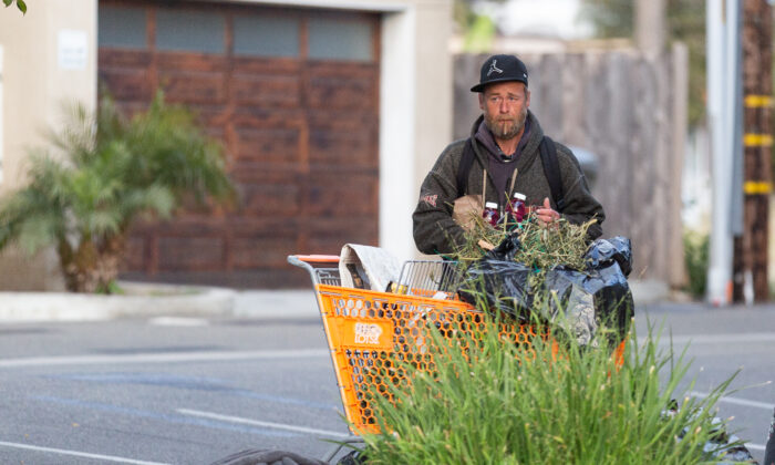 A homeless person stands next to his cart in a parking lot in Oceanside, Calif., on April 14, 2021. (John Fredricks/The Epoch Times)