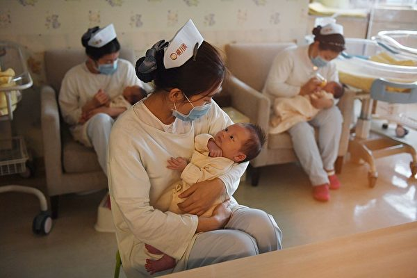 """Nurses hold babies at the Xiyuege Centre, or """"Lucky Month Home,"""" in Beijing, on Dec. 13, 2016. (Greg Baker/AFP via Getty Images)"""