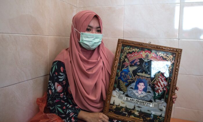 Berda Asmara shows a photo of her sailor husband Mes Guntur Ari Prasetyo at their home in Surabaya on April 23, 2021. (Juni Kriswanto / AFP via Getty Images)