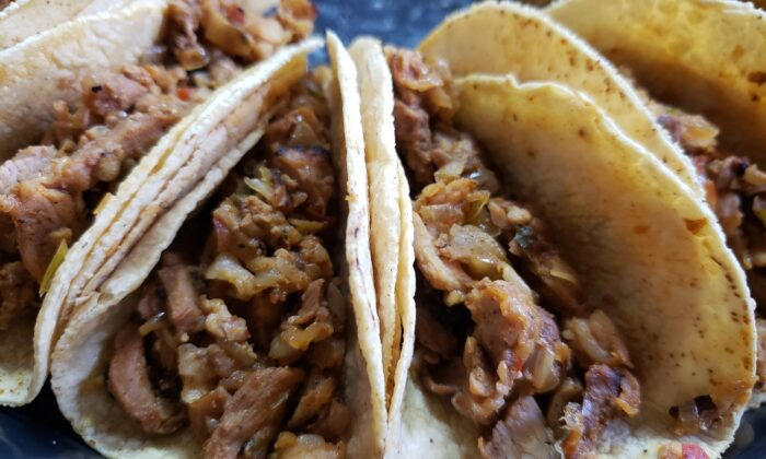 Celebrate Cinco de Mayo with these citrus-marinated pork tacos, served with side dishes of guacamole, sour cream, and salsa. (Dreamstime/TNS)