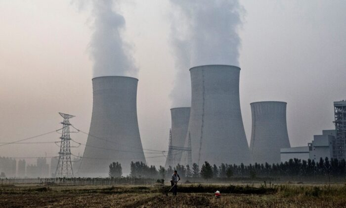 A Chinese farmer works his field next to a state-owned, coal-fired power plant in Huainan, Anhui province, China, on June 15, 2017. (Kevin Frayer/Getty Images)