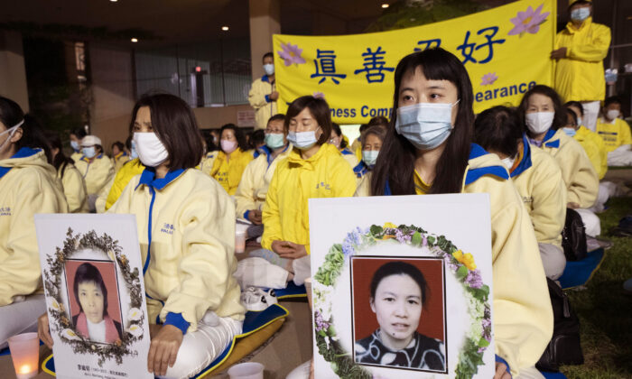 Falun Dafa practitioners hold photos of some of those who were killed during the 22-year persecution by the Chinese Communist Party in China, at a candlelight vigil in Los Angeles on April 23, 2021. (Debora Cheng/The Epoch Times)
