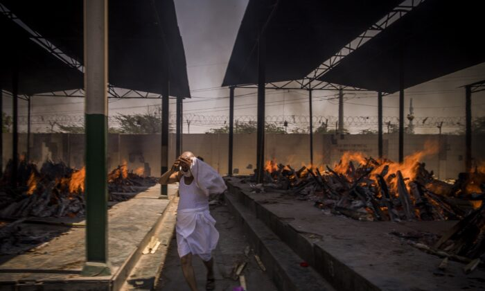 A priest who helps perform last rites runs while covering his face amid the multiple funeral pyres of people who died of COVID-19, at a crematorium in New Delhi, India, on April 24, 2021. (Anindito Mukherjee/Getty Images)