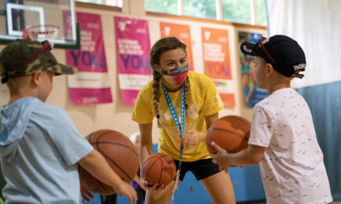 A counselor wearing a protective face mask plays with children as summer camps reopen amid the spread of coronavirus disease (COVID-19) at Carls Family YMCA summer camp in Milford, Mich., on June 23, 2020. (Emily Elconin/Reuters,File Photo)