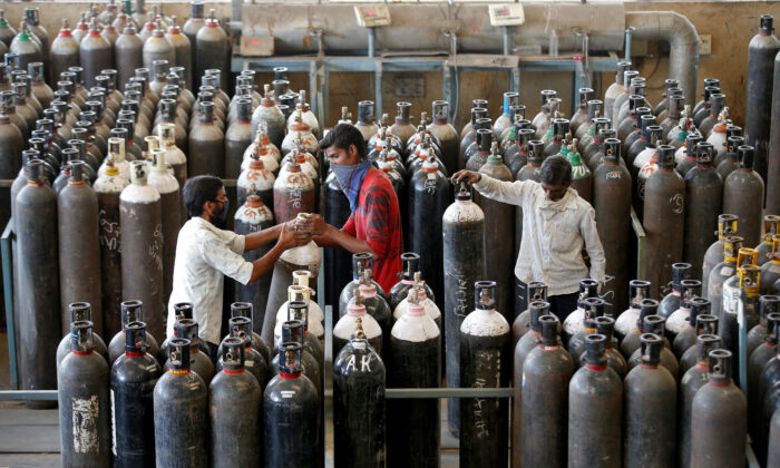 People carry oxygen cylinders after refilling them in a factory, amidst the spread of the CCP virus disease (COVID-19) in Ahmedabad, India, on April 25, 2021. (Amit Dave/Reuters)