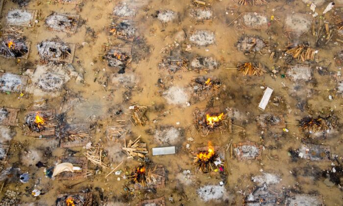 In this aerial picture taken on April 26, 2021, burning pyres of victims who lost their lives due to the Covid-19 coronavirus are seen at a cremation ground in New Delhi. (Jewel Samad/AFP via Getty Images)