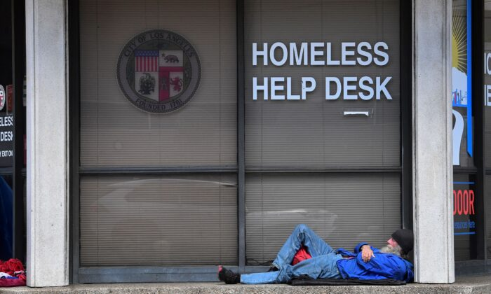 A man sleeps outside the Homeless Help Desk kiosk in the Skid Row community of Los Angeles, Calif., on April 26, 2021. (Frederic J. Brown/AFP via Getty Images)