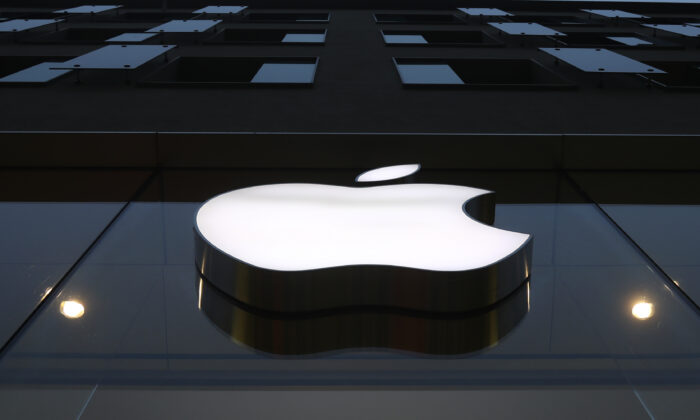 The logo of Apple is illuminated at a store in the city center in Munich, on April 26, 2021. (AP Photo/Matthias Schrader, File)