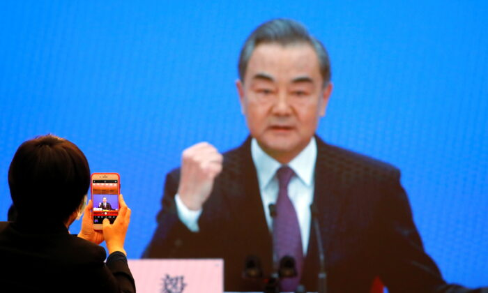 Chinese State Councillor and Foreign Minister Wang Yi is displayed on a screen as he attends via video link a news conference on the sidelines of the National People's Congress (NPC), in Beijing, China on March 7. (Reuters/Thomas Peter)
