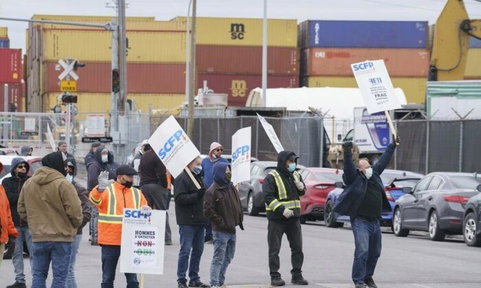 Striking dockworkers from the Port of Montreal walk the picket line during the first day of a strike in Montreal on April 26, 2021. Federal Labour Minister Filomena Tassi has tabled a bill to put an end to the strike involving 1,150 dockworkers at the Port of Montreal. (Paul Chiasson/The Canadian Press)