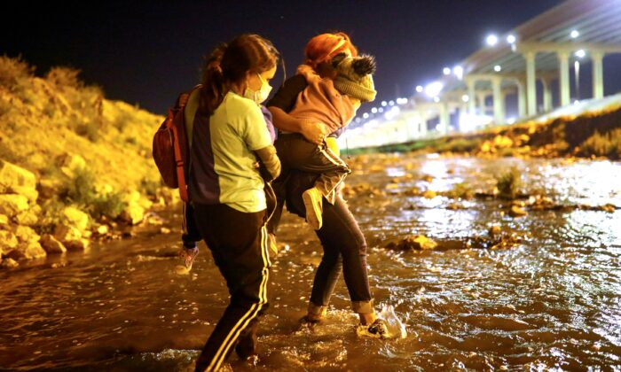 """A woman and her children, accompanied by a human smuggler or """"coyote"""" (R), cross the Rio Bravo river to El Paso, Texas, as seen from Ciudad Juarez, Mexico, on March 30, 2021. (Edgard Garrido/Reuters)"""