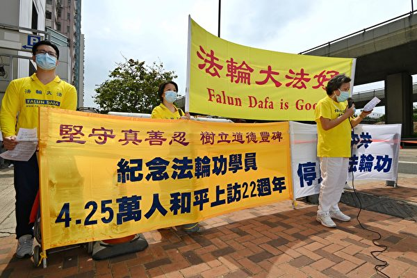 Four Falun Gong practitioners in front of the Liaison Office in Hong Kong on April 25, 2021, to commemorated the 22nd anniversary of a historical appeal for freedom of belief in mainland China. (Song Bilong/The Epoch Times)