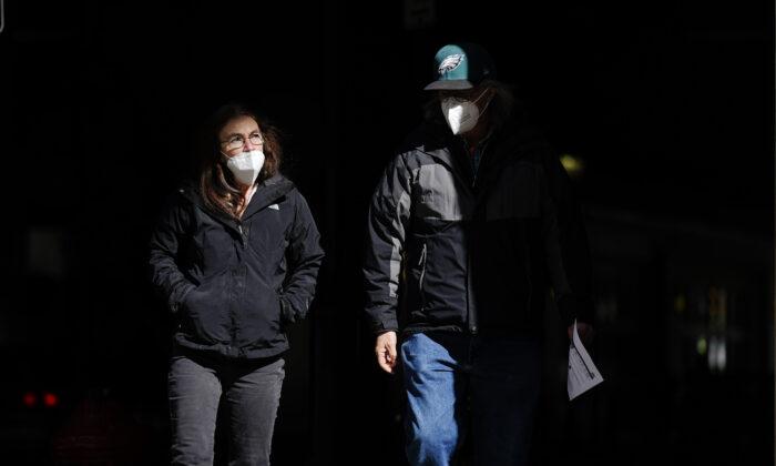 People wearing masks walk through a shaft of light on a street in Philadelphia, Pa., on March 3, 2021. (Matt Rourke/AP Photo)