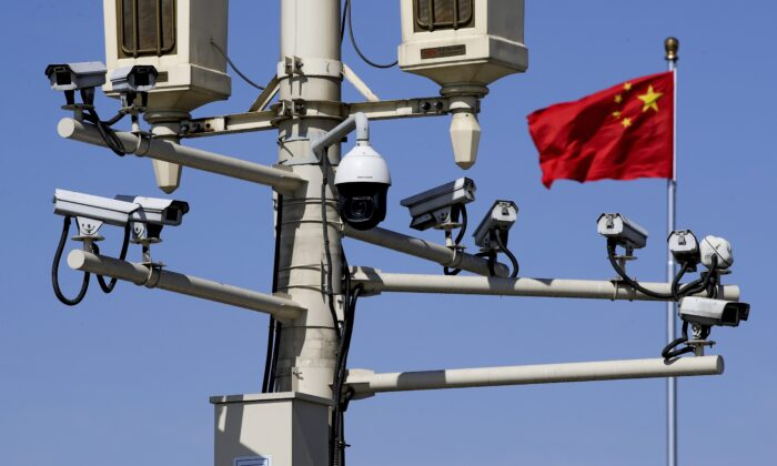 A Chinese national flag flutters near the surveillance cameras mounted on a lamp post in Tiananmen Square in Beijing, China, on March 15, 2019. (Andy Wong/AP Photo)