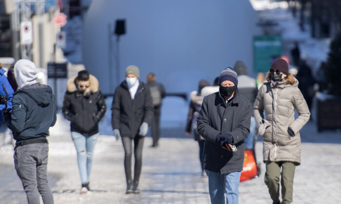 People walk along a street in Montreal on Feb. 21, 2021, as the COVID-19 pandemic continues in Canada and around the world.  (The Canadian Press/Graham Hughes)