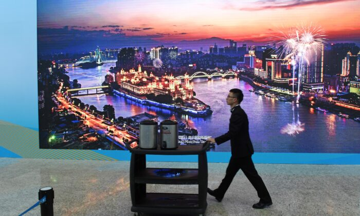 A worker pushes a cart past a screen showing a photo of the Fujian Pilot Free Trade Zone, at the venue of the Belt and Road Forum in Beijing on April 26, 2019. (Greg Baker/AFP via Getty Images)