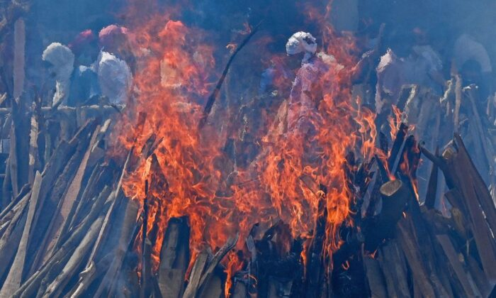 Family members and relatives perform the last rites amid the funeral pyres of victims who died of the Covid-19 coronavirus during mass cremation held at a crematorium in New Delhi on April 27, 2021. (Prakash Singh/Getty Images)