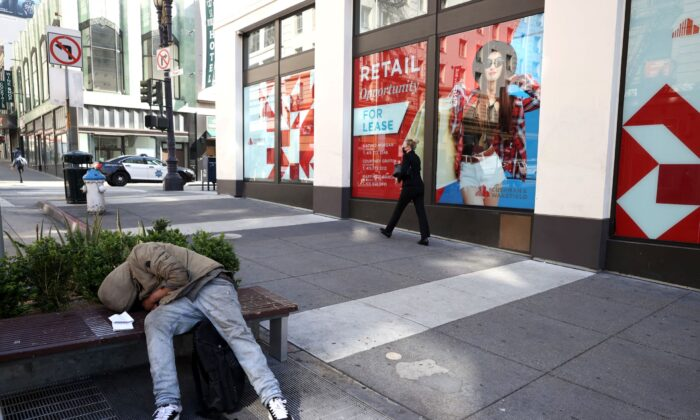 A homeless person sleeps on a bench in front of closed retail stores in San Francisco, Calif., on April 16, 2021. (Justin Sullivan/Getty Images)