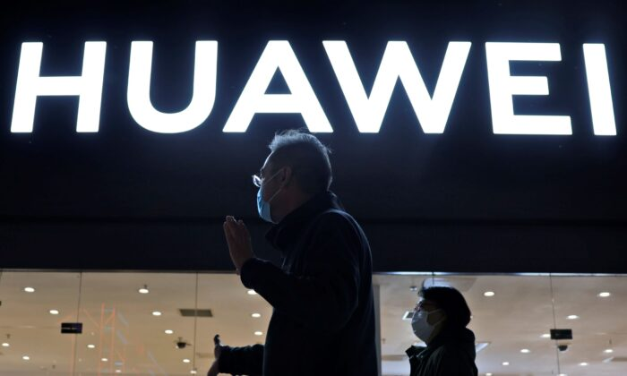 Residents pass by a Huawei electronics store in Beijing, on April 12, 2021. (Ng Han Guan/AP Photo)