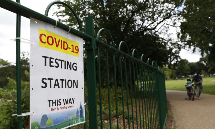 People walk past a sign directing to a walk-in mobile COVID-19 testing centre in Spinney Hill Park in Leicester, England, on June 28, 2020. (Darren Staples/Getty Images)