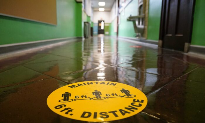 A social distancing reminder is posted on a hallway floor of Nebinger Elementary School in Philadelphia, Pa., on March 19, 2021. (Matt Rourke/AP Photo)