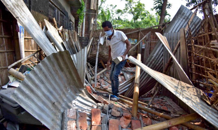 A man searches for his belongings amidst the debris after a boundary wall of his house collapsed following an earthquake in Nagaon district in the northeastern state of Assam, India, April 28, 2021. (Anuwar Hazarika/Reuters)