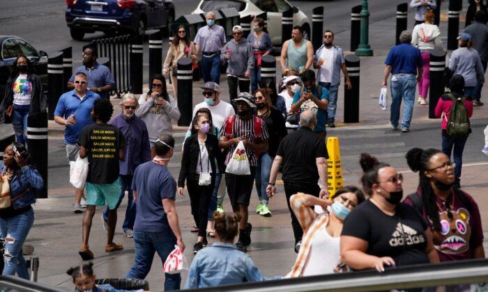 Masked and unmasked pedestrians walk along the Las Vegas Strip in Las Vegas, on April 27, 2021. (John Locher/AP Photo)