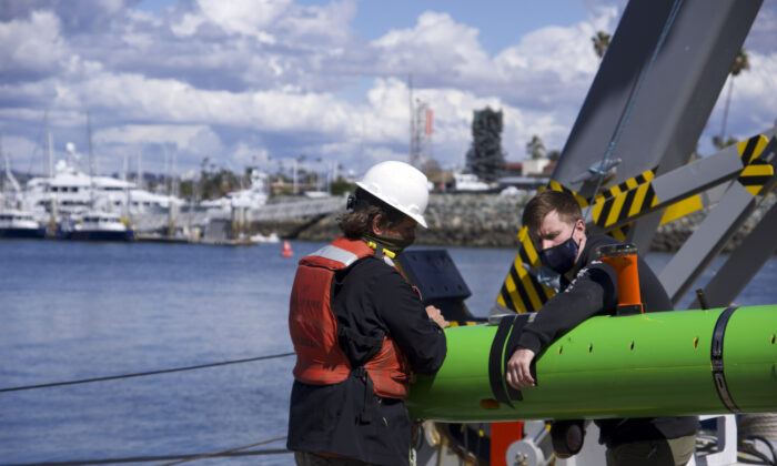 In this March 2021 image provided by Scripps Institution of Oceanography at UC San Diego, researchers aboard the research vessel Sally Ride recover an autonomous underwater vehicle after a search for discarded barrels near Santa Catalina Island, Calif. (Scripps Institution of Oceanography at UC San Diego via AP)