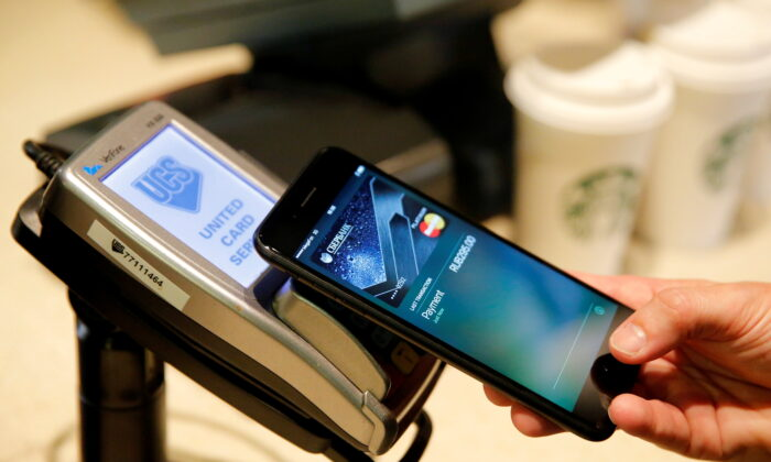 A man uses an iPhone 7 smartphone to demonstrate the mobile payment service Apple Pay at a cafe in Moscow, Russia, on Oct. 3, 2016. (Maxim Zmeyev/Reuters)