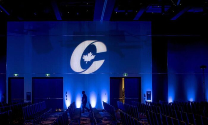A man is silhouetted walking past a Conservative Party logo before the opening of the Party's national convention in Halifax on Aug. 23, 2018. The Conservative Party of Canada says it raised a record $8.47 million in the first quarter of 2021.  (Darren Calabrese / The Canadian Press)