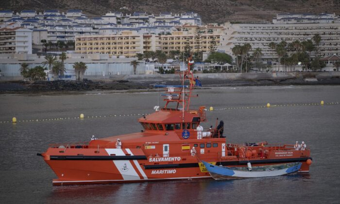 A wooden boat is towed by a Spanish Maritime Rescue Service ship as they arrive at the port of Los Cristianos in the south of Tenerife, in the Canary Islands, Spain, on April 28, 2021. (Andres Gutierrez/AP Photo)