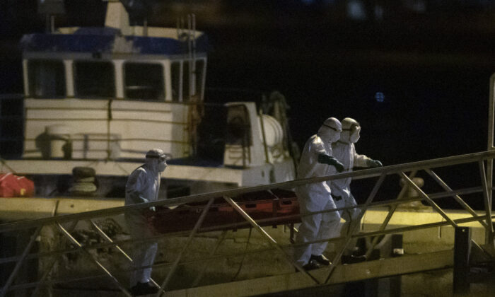 Emergency services carry dead bodies of migrants after being recovered from a wooden boat at the port of Los Cristianos in the south of Tenerife, in the Canary Island, Spain, on April 28, 2021. (Andres Gutierrez/AP Photo)