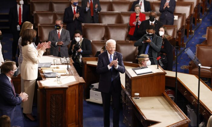 President Joe Biden applauds along with Vice President Kamala Harris, Speaker of the House Nancy Pelosi and members of Congress as he arrives to address a socially distant joint session in the House chamber of the Capitol in Washington on April 28, 2021. (Jonathan Ernst/Pool/Getty Images)