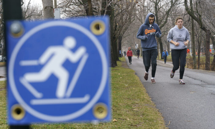 People jog in a park on a warm fall day in Montreal on Dec. 1, 2020. (The Canadian Press/Paul Chiasson)