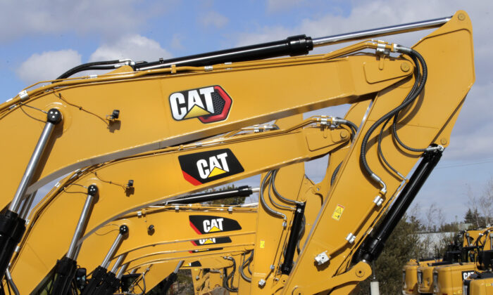 "Excavator booms, adorned with the Caterpillar Inc. ""CAT"" logo are displayed at the Milton CAT dealership in Londonderry, N.H., on Feb. 20, 2020. (Charles Krupa/AP Photo)"