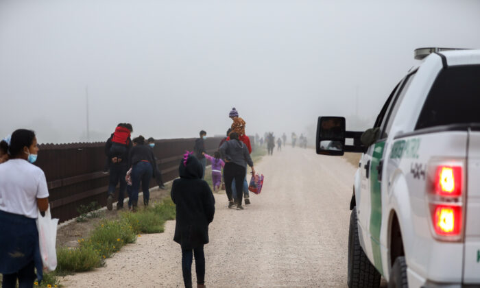 A group of illegal immigrants with Border Patrol after crossing the U.S.–Mexico border in La Joya, Texas, on April 10, 2021. (Charlotte Cuthbertson/The Epoch Times)