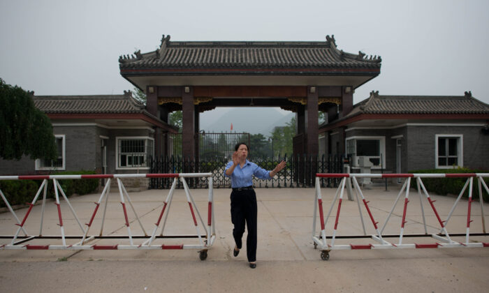 A policewoman approaches to stop the taking of photos at the entrance to Qincheng prison on the outskirts of Beijing on Sept. 12, 2013. (Ed Jones/AFP via Getty Images)