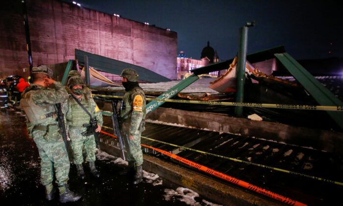 """Soldiers chat at a scene where the roof protecting the """"Casa de las Aguilas"""", part of the ruins of the Templo Mayor archaeological site, collapsed after heavy rain and hail, in downtown Mexico City, Mexico, on April 28, 2021. (Gustavo Graf/Reuters)"""
