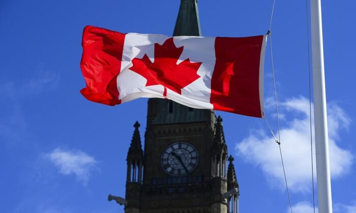 The House of Commons returns today to sit for five weeks following the Easter break. A Canada flag is pictured with the Peace Tower on Parliament Hill in Ottawa on April 12, 2021. (The Canadian Press/Sean Kilpatrick)
